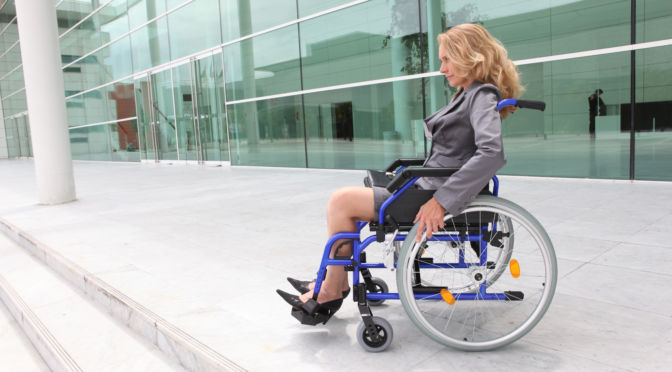 Imagen de una persona en silla de ruedas al inicio de una escalera